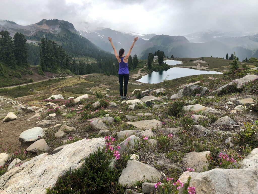 Woman standing with arms outstretched on the Elfin Lakes Hike with BeWild Adventures