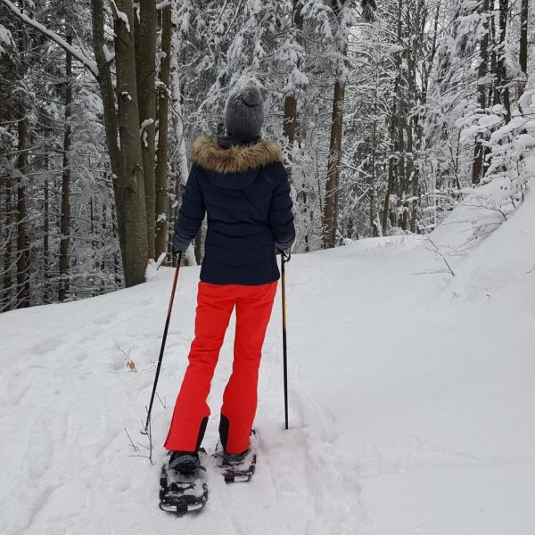 Person snowshoeing in BC in a dark jacket and bright red snowpants
