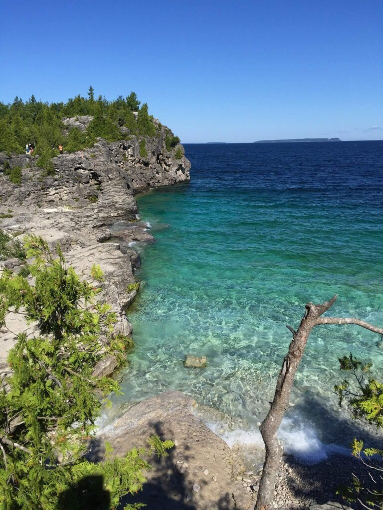 Crystal clear turquoise water at the base of steep rocky cliffs on the Bruce Peninsula in Ontario