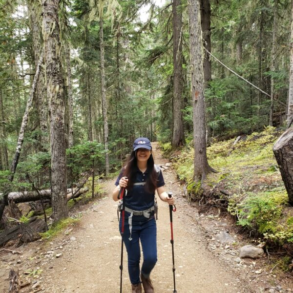 11A woman posing on a hiking trail in BC with hiking poles
