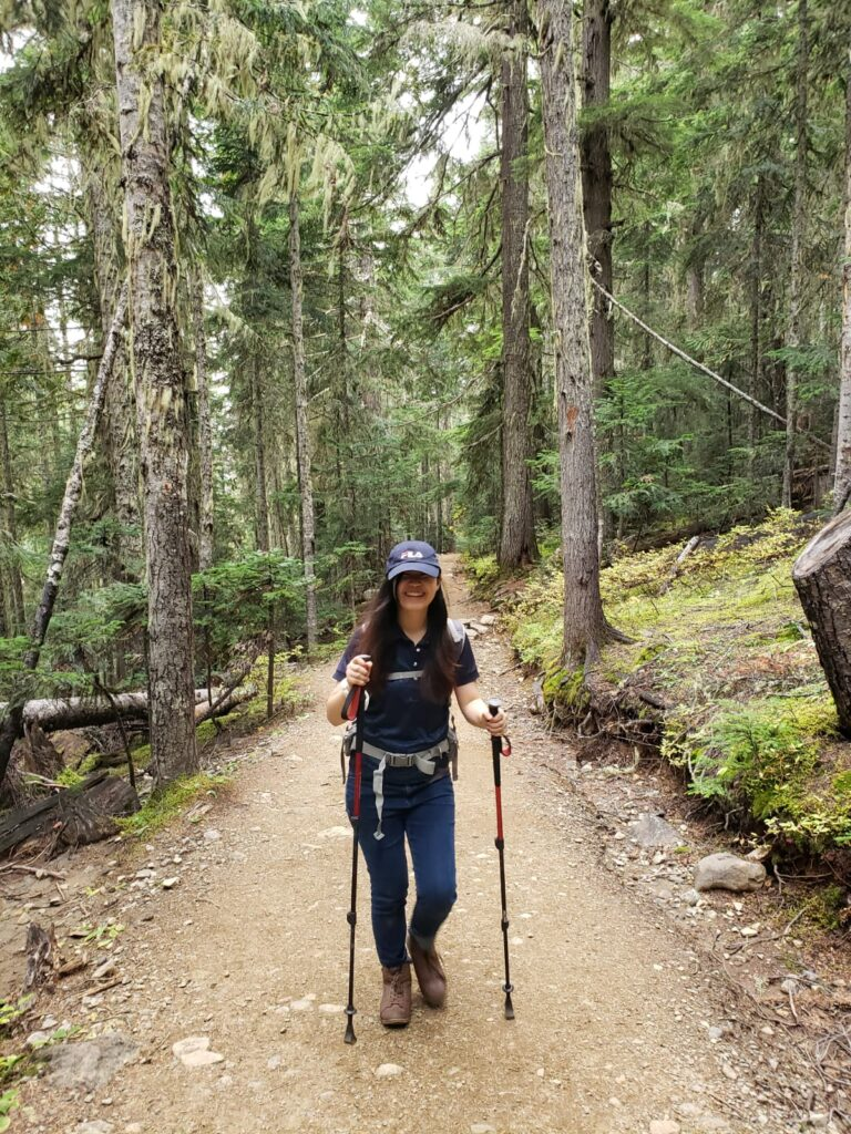 A woman posing on a hiking trail in BC with hiking poles